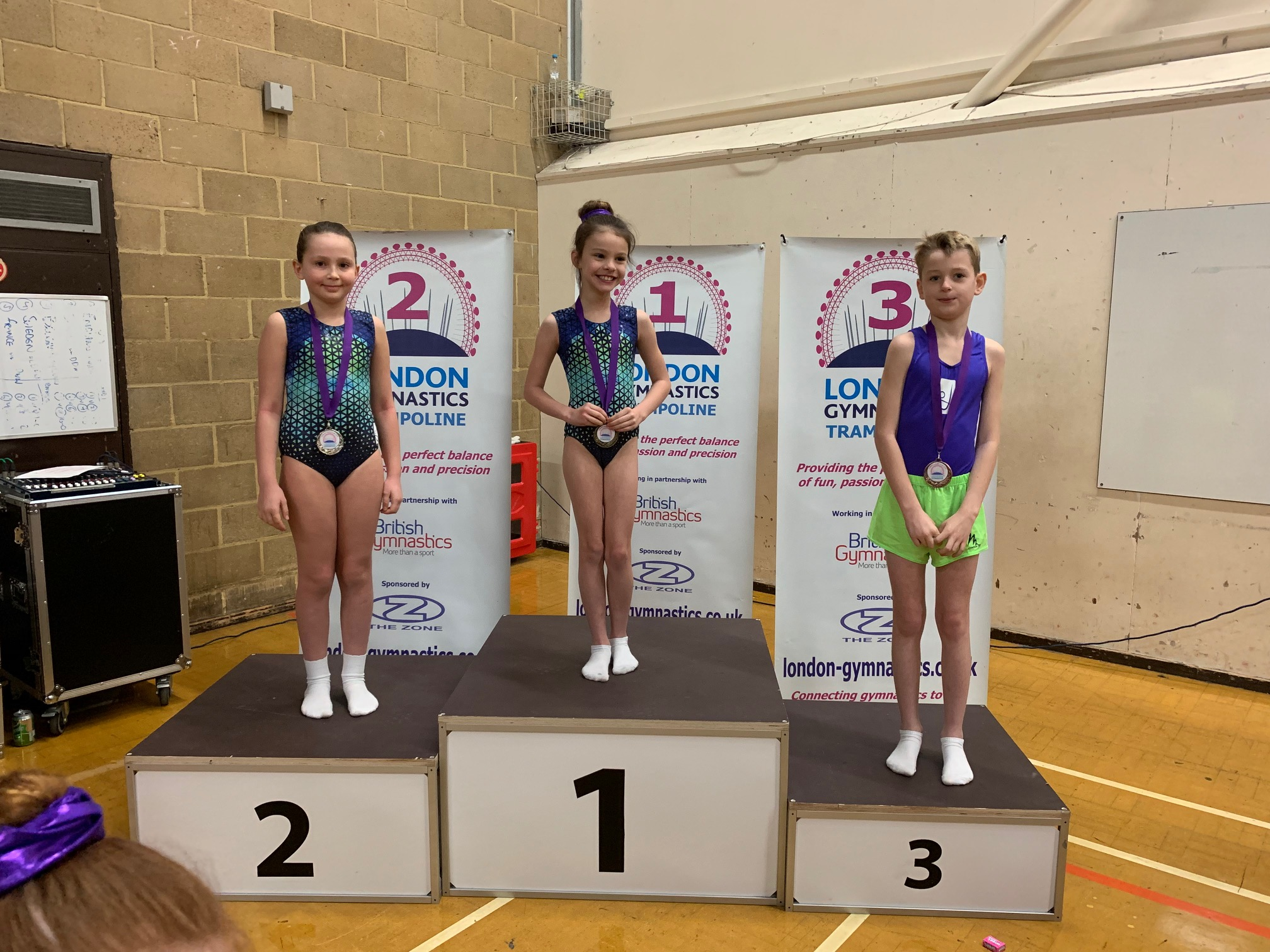 3 young trampoline gymnasts stand on a prize giving podium
