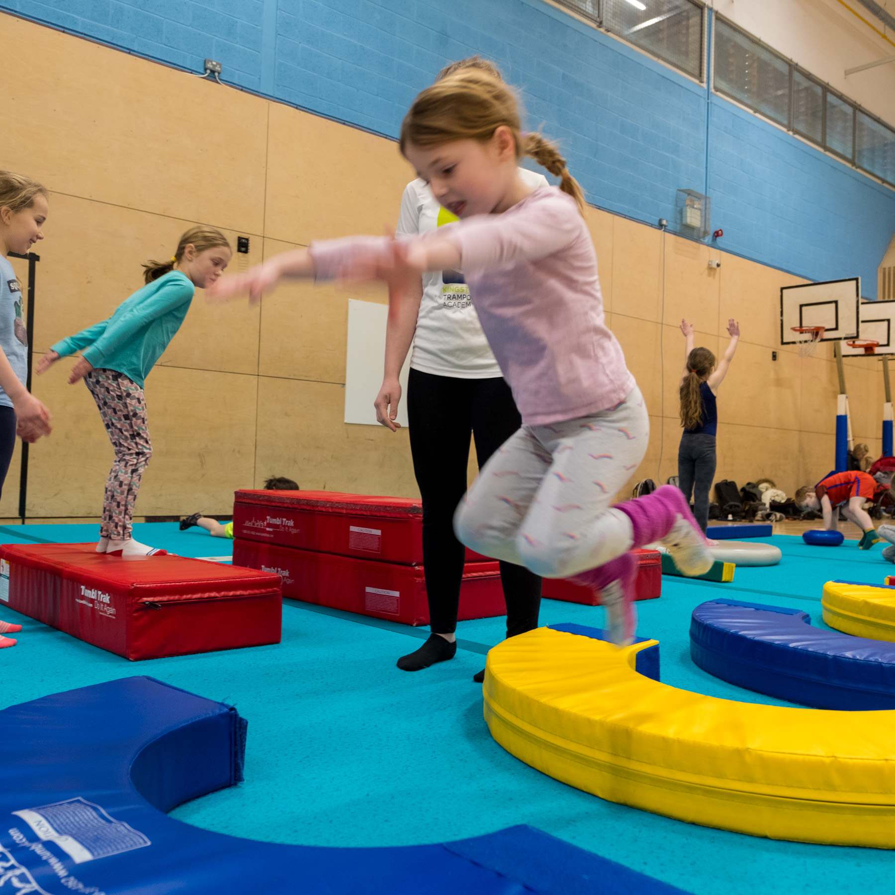 Girl jumping on soft play equipment, to help preare to make the most of time on the trampoline